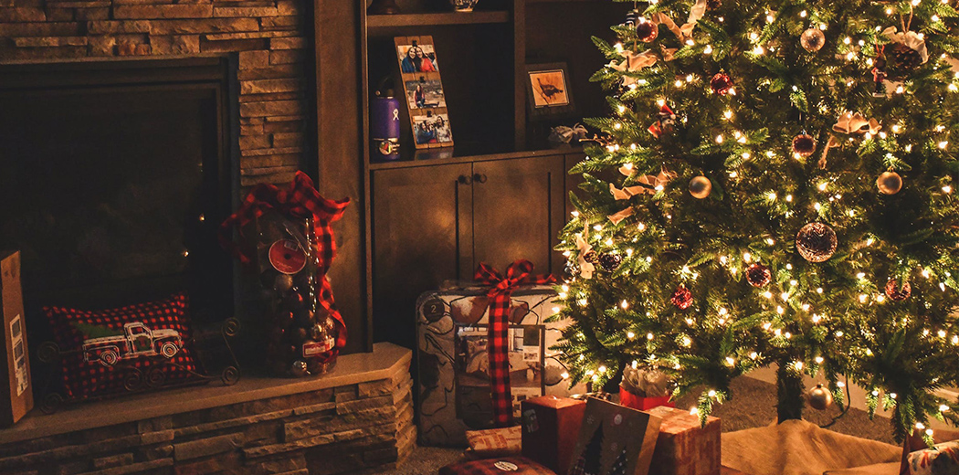 Christmas tree and presents next to fireplace